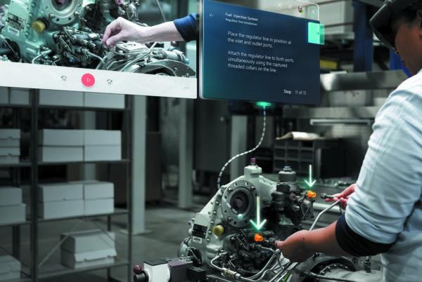 Работник завода выполняет сборку двигателя